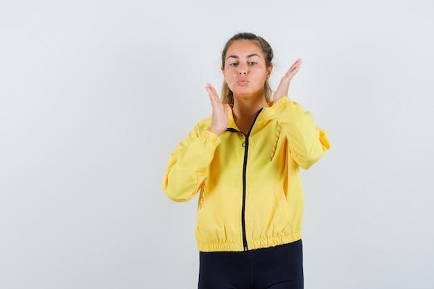 Mulher loira de mãos dadas perto do rosto e mandando beijos em uma jaqueta amarela e calça preta e parecendo séria