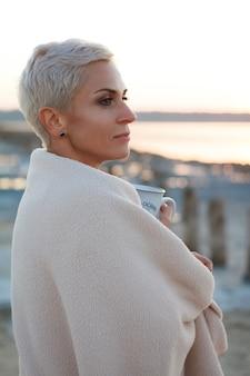 Mulher loira de meia idade adulta se envolveu em uma manta brilhante na praia e olha para o mar