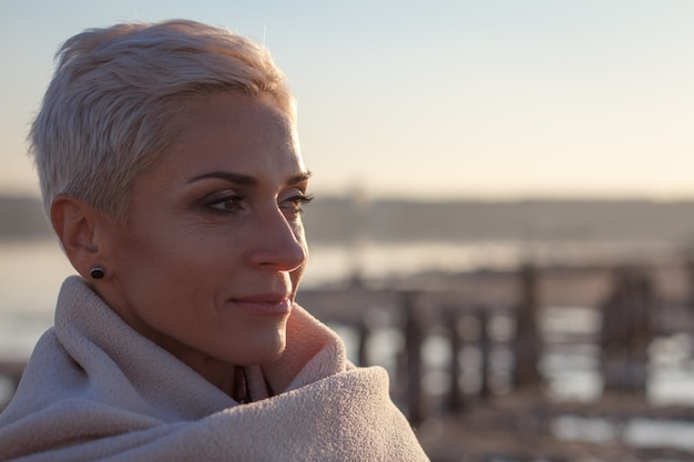 Mulher loira de meia idade adulta se envolveu em uma manta brilhante na praia