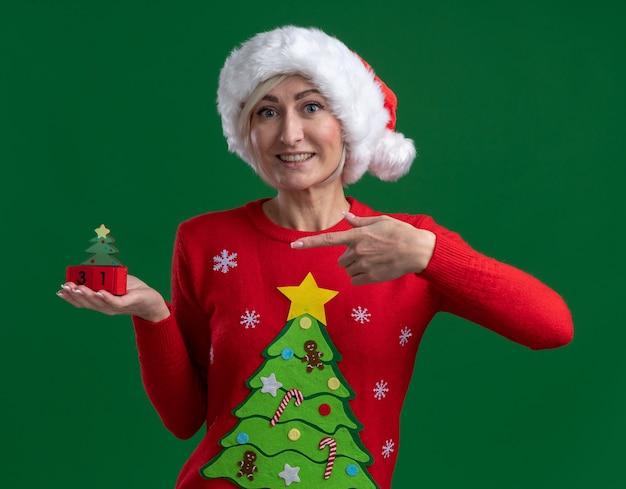 Mulher loira de meia-idade alegre com chapéu de natal e suéter segurando e apontando para o brinquedo da árvore de natal com data olhando para a câmera isolada no fundo verde