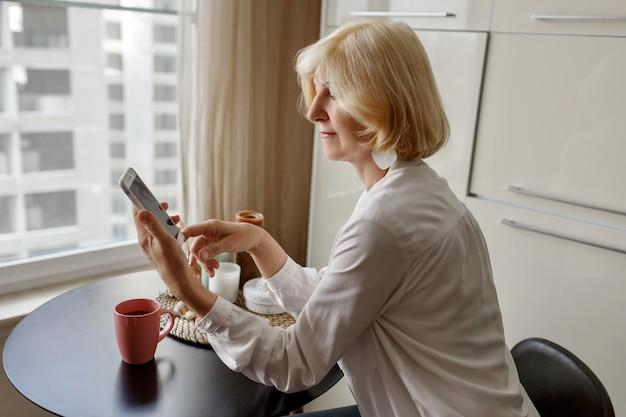 Mulher loira de meia idade atraente relaxando em casa na cozinha e falando pelo telefone móvel