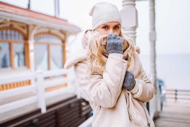 Mulher loira de meia-idade bonita aproveite o tempo ao ar livre no dia de inverno. mulher vestindo uma jaqueta leve, chapéu e lenço.