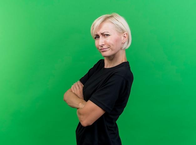 Mulher loira de meia-idade carrancuda em pé com postura fechada em vista de perfil, olhando para a frente isolada na parede verde