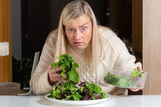 Mulher loira de meia idade com expressão facial insatisfeita, preparando salada verde na cozinha, alimentação saudável e conceito de dieta