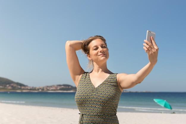 Mulher loira de meia-idade com um vestido verde, fazendo um selfie na praia.