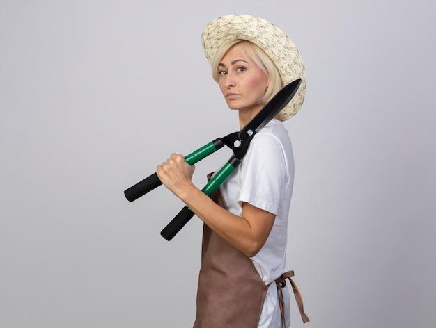 Mulher loira de meia-idade confiante, de uniforme, usando um chapéu