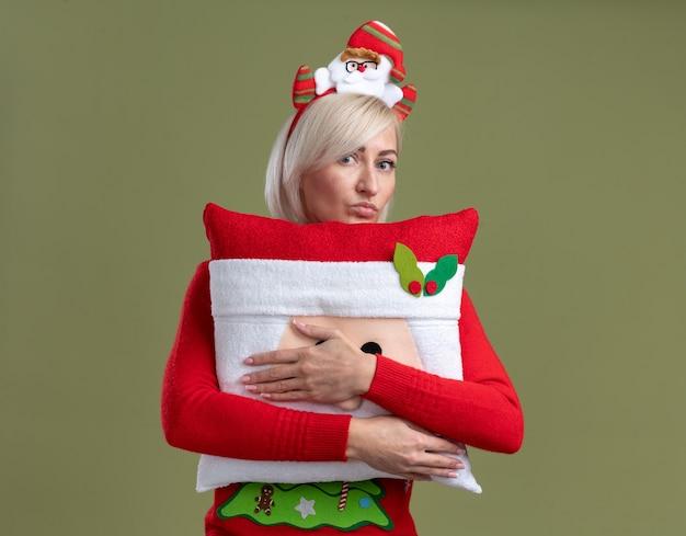 Mulher loira de meia-idade confiante usando bandana de papai noel e suéter de natal abraçando o travesseiro de papai noel, parecendo com os lábios franzidos, isolado na parede verde oliva com espaço de cópia