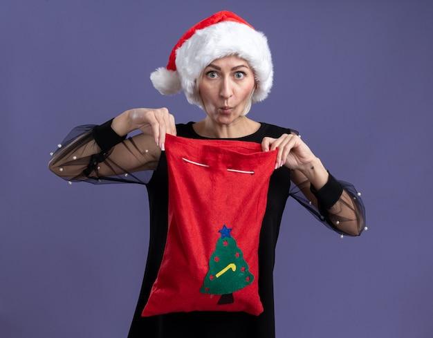 Mulher loira de meia-idade curiosa usando um chapéu de natal segurando um saco de natal, abrindo-o e olhando para a câmera com os lábios franzidos, isolados no fundo roxo