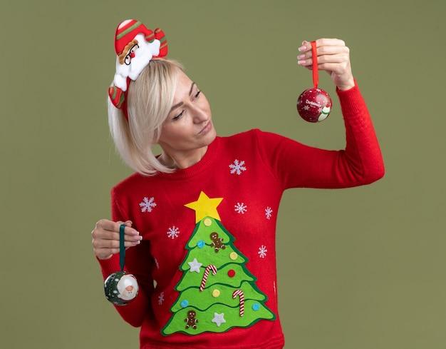 Mulher loira de meia-idade duvidosa usando bandana de papai noel e suéter de natal segurando enfeites de natal olhando para um isolado em fundo verde oliva