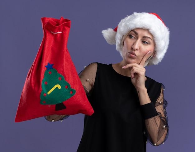 Mulher loira de meia-idade duvidosa usando chapéu de natal segurando um saco de natal olhando para ele mantendo a mão no queixo isolado no fundo roxo