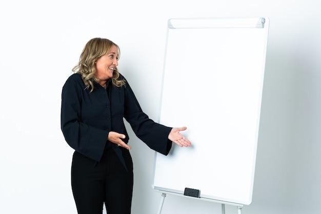 Mulher loira de meia-idade em branco isolado fazendo uma apresentação no quadro branco e com expressão de surpresa