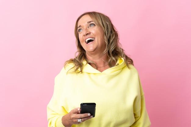 Mulher loira de meia-idade em rosa isolada usando telefone celular