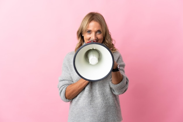 Mulher loira de meia-idade em um fundo rosa isolado gritando em um megafone para anunciar algo