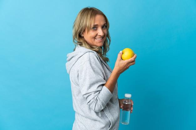Mulher loira de meia-idade em uma parede isolada com uma maçã e uma garrafa de água