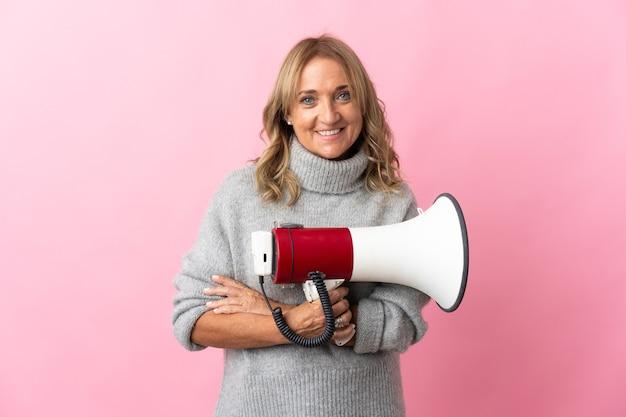 Mulher loira de meia-idade em uma parede rosa isolada segurando um megafone e sorrindo