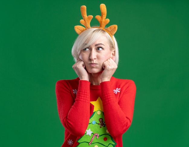 Mulher loira de meia-idade entediada usando tiara de chifres de rena de natal e suéter de natal olhando para o lado com bochechas inchadas, mantendo as mãos no rosto isoladas sobre fundo verde