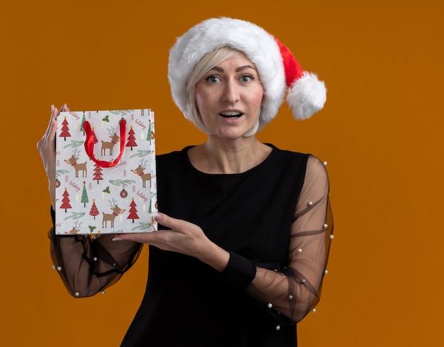 Mulher loira de meia-idade impressionada com chapéu de natal, olhando para a câmera, mostrando a sacola de presente de natal para a câmera isolada em fundo laranja