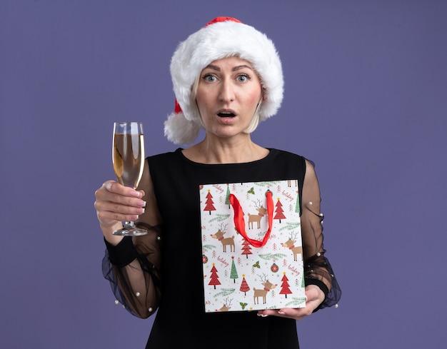 Mulher loira de meia-idade impressionada com chapéu de natal olhando para a câmera segurando uma taça de champanhe e uma sacola de presente de natal isolada no fundo roxo