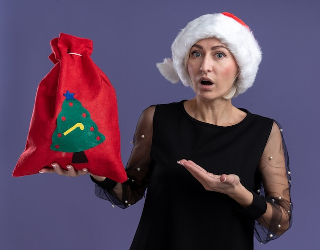 Mulher loira de meia-idade impressionada com chapéu de natal segurando e apontando com a mão para o saco de natal, olhando para a câmera isolada no fundo roxo