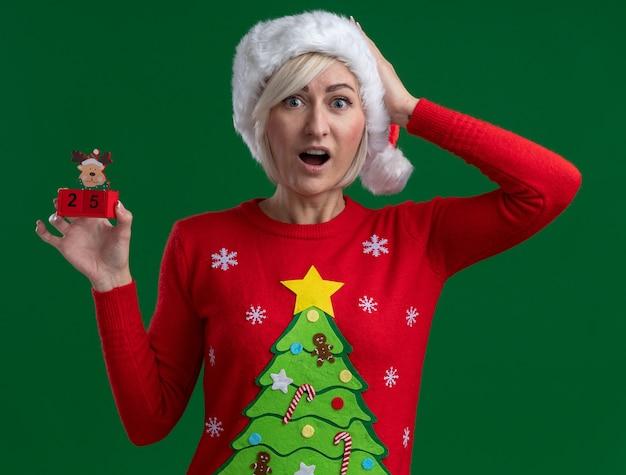 Mulher loira de meia-idade impressionada com chapéu e suéter de natal segurando um brinquedo de rena de natal com uma data olhando para a câmera, mantendo a mão na cabeça isolada sobre fundo verde