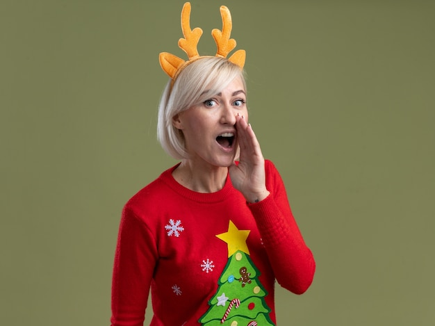 Mulher loira de meia-idade impressionada usando bandana de chifres de rena de natal e suéter de natal procurando manter a mão perto da boca sussurrando isolado na parede verde oliva com espaço de cópia
