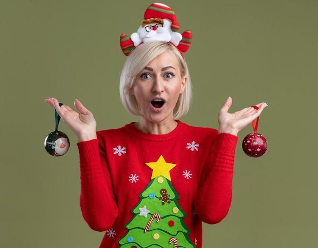 Mulher loira de meia-idade impressionada usando bandana de papai noel e suéter de natal segurando enfeites de natal olhando para a câmera isolada em fundo verde oliva