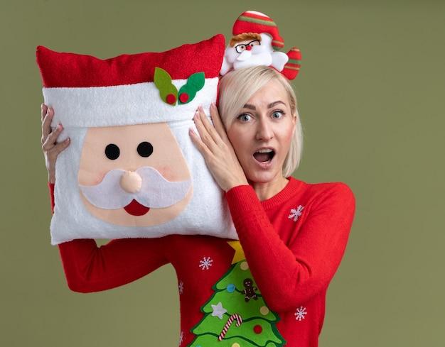 Mulher loira de meia-idade impressionada usando bandana de papai noel e suéter de natal segurando uma almofada de papai noel tocando a cabeça com ela olhando para a câmera isolada em fundo verde oliva