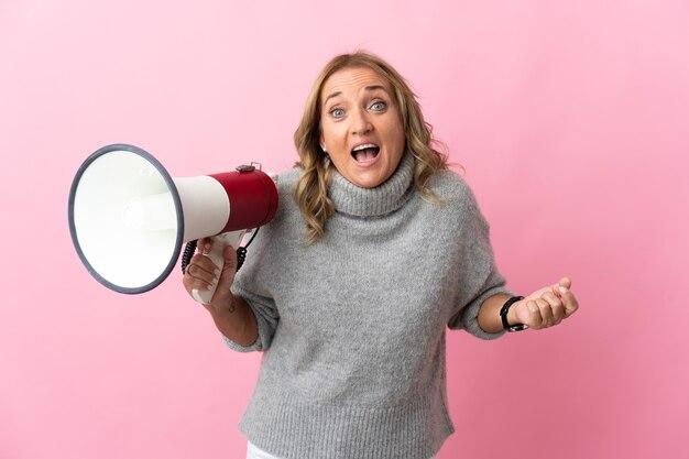Mulher loira de meia-idade isolada rosa segurando um megafone e com expressão de surpresa