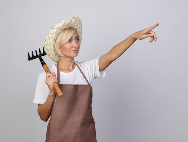 Mulher loira de meia-idade, jardineira, de uniforme, usando chapéu, segurando o ancinho no ombro, olhando e apontando para cima, isolado na parede branca