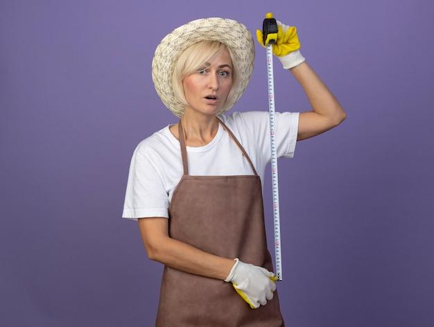 Mulher loira de meia-idade, jardineira, impressionada, de uniforme, usando chapéu e luvas de jardinagem, olhando para a frente, segurando o medidor de fita isolante na parede roxa com espaço de cópia