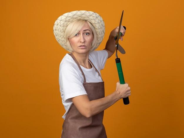 Mulher loira de meia-idade, jardineira, impressionada, de uniforme, usando um chapéu em pé na vista de perfil, segurando uma tesoura de cerca viva isolada na parede laranja com espaço de cópia