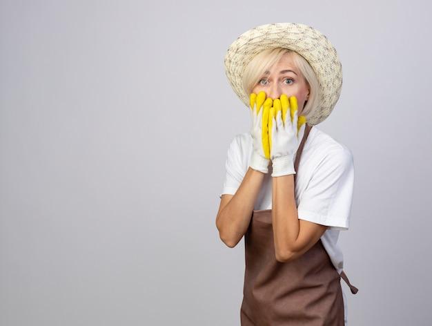 Mulher loira de meia-idade, jardineira preocupada, de uniforme, usando chapéu e luvas de jardinagem