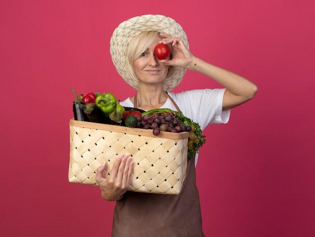 Mulher loira de meia-idade, jardineira, satisfeita de uniforme, usando um chapéu, segurando uma cesta de legumes e tomate na frente do olho, olhando para a frente, isolada na parede carmesim