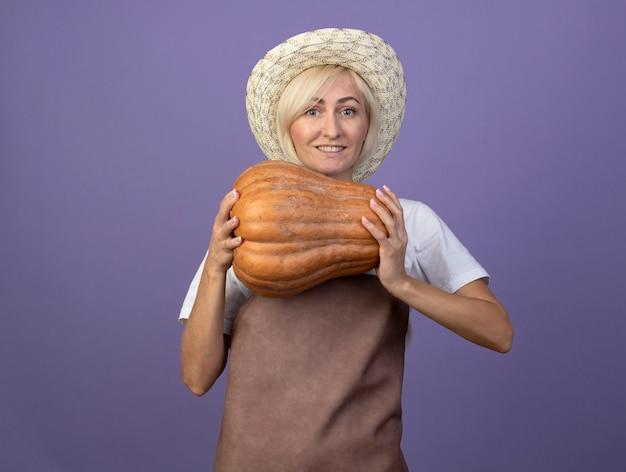 Mulher loira de meia-idade, jardineira, sorridente, de uniforme, usando um chapéu, segurando uma abóbora de abóbora olhando para a frente, isolada na parede roxa com espaço de cópia