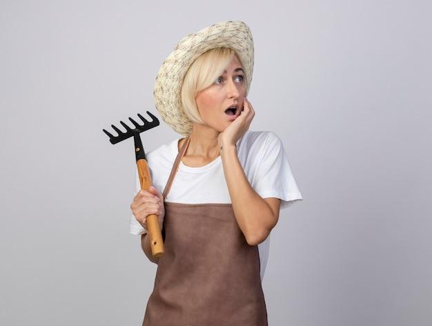 Mulher loira de meia-idade, jardineira, surpresa, usando um chapéu, segurando o ancinho, colocando a mão no queixo, olhando para o lado isolado no fundo branco com espaço de cópia