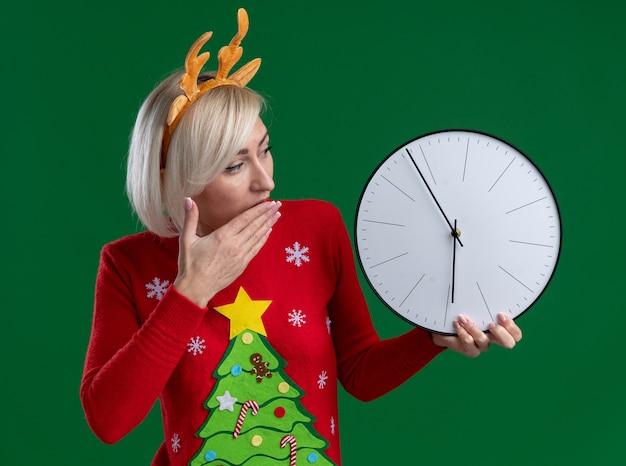 Mulher loira de meia-idade preocupada usando bandana de chifres de rena de natal e suéter de natal segurando e olhando para o relógio, mantendo a mão na boca isolada na parede verde