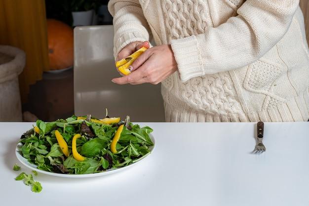 Mulher loira de meia idade preparando salada verde na cozinha, conceito de alimentação e dieta saudável, close-up
