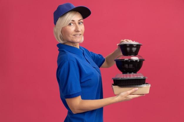 Mulher loira de meia-idade satisfeita com um entregador de uniforme azul e boné em pé na vista de perfil, segurando um pacote de comida de papel e recipientes de comida isolados na parede rosa com espaço de cópia