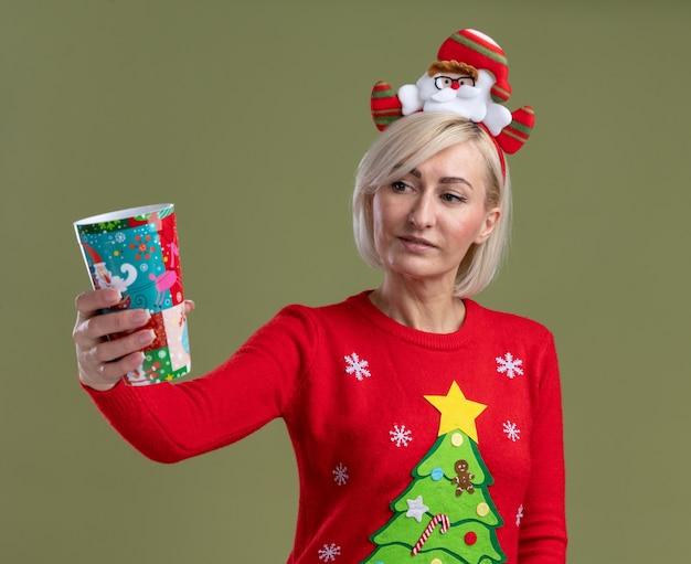 Mulher loira de meia-idade satisfeita usando bandana de papai noel e suéter de natal esticando o copo de plástico de natal em direção à câmera, olhando para ele isolado na parede verde oliva