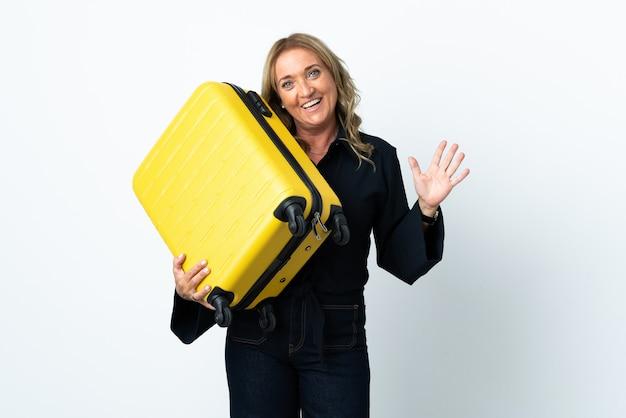Mulher loira de meia-idade sobre fundo branco isolado em férias com mala de viagem e fazendo sinal de ok