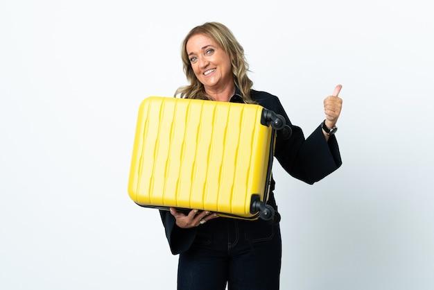 Mulher loira de meia-idade sobre fundo branco isolado nas férias com mala de viagem e polegar para cima