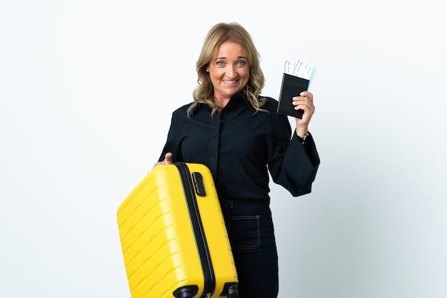 Mulher loira de meia-idade sobre fundo branco isolado nas férias com mala e passaporte