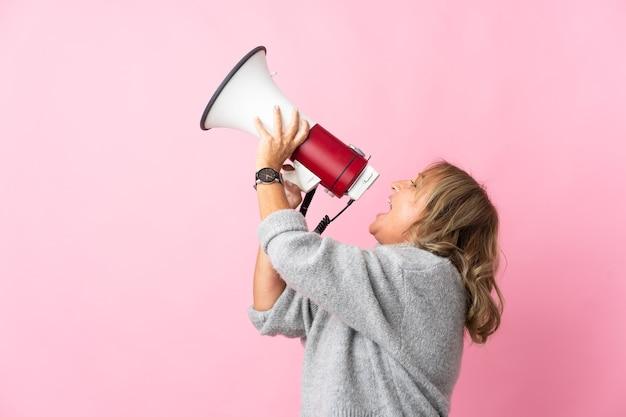Mulher loira de meia-idade sobre um fundo rosa isolado gritando em um megafone para anunciar algo na posição lateral