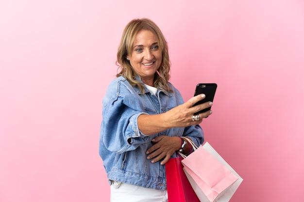 Mulher loira de meia-idade sobre um fundo rosa isolado segurando sacolas de compras e escrevendo uma mensagem com seu telefone celular para um amigo