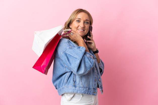 Mulher loira de meia-idade sobre um fundo rosa isolado segurando sacolas de compras e ligando para um amigo com o celular