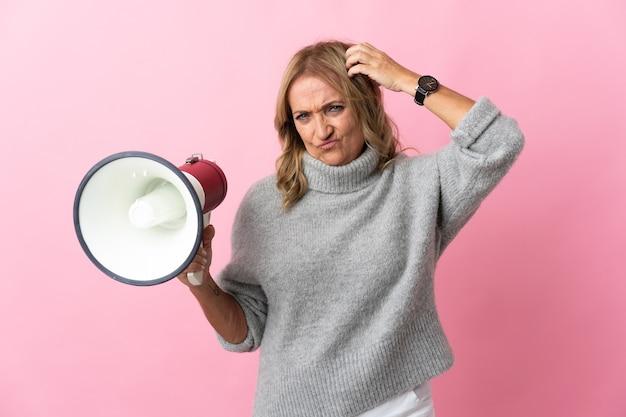 Mulher loira de meia-idade sobre um fundo rosa isolado segurando um megafone e tendo dúvidas