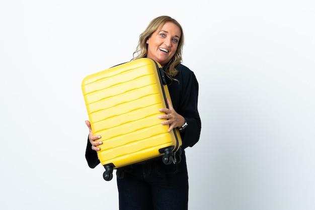 Mulher loira de meia-idade sobre uma parede branca isolada nas férias com mala de viagem e surpresa