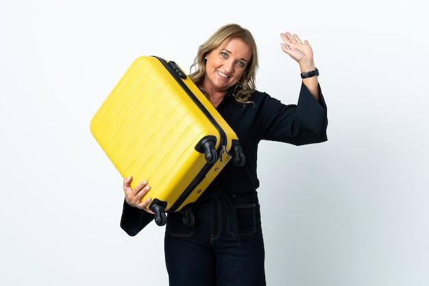 Mulher loira de meia-idade sobre uma parede branca isolada nas férias com uma mala de viagem e saudando