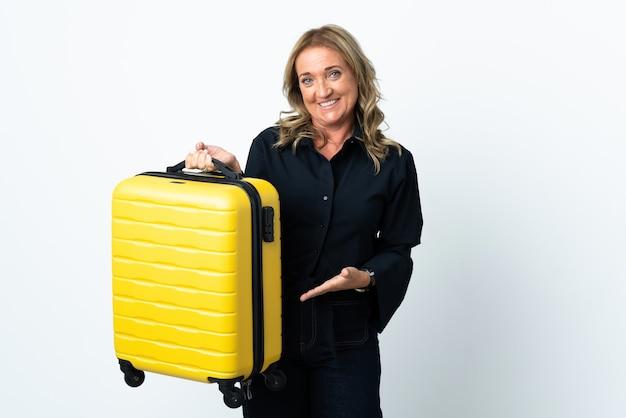 Mulher loira de meia-idade sobre uma parede branca isolada nas férias com uma mala de viagem