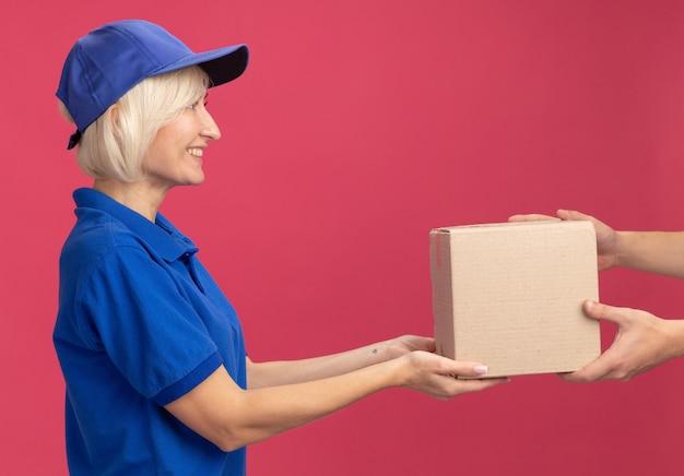 Mulher loira de meia-idade, sorridente, entregadora de uniforme azul e boné em vista de perfil, dando uma caixa de papelão para o cliente, olhando para o cliente isolado na parede rosa